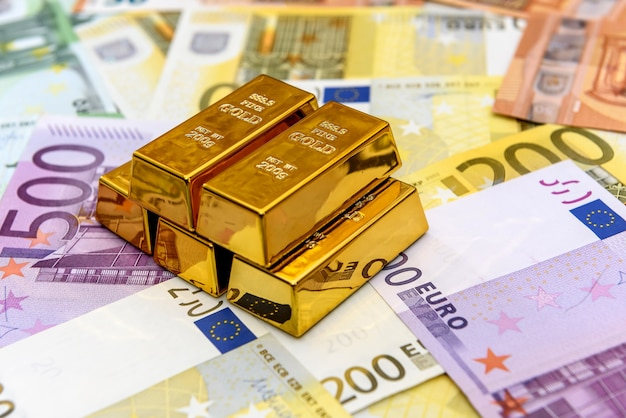 Gold bullions at euro banknotes closeup