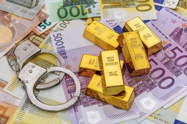 Gold bullions with handcuffs at euro banknotes