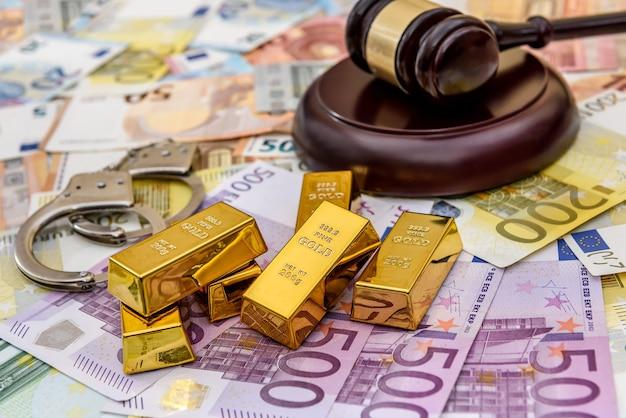 Золотые слитки с молотком судьи и наручниками на банкнотах евро
