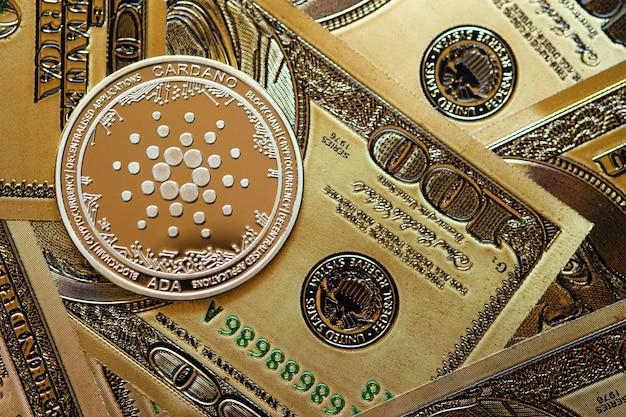 골드 카르다노 암호화폐 동전과 100달러 지폐 배경