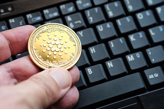 골드 카르다노 암호화폐 동전과 컴퓨터 키보드 배경