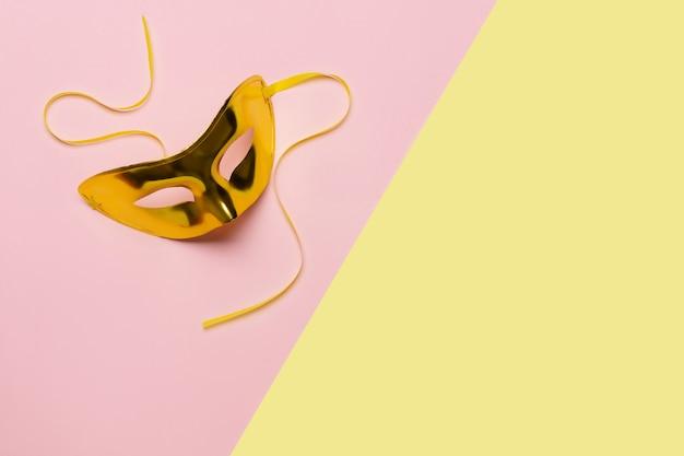 Золотая карнавальная маска на желто-розовом фоне