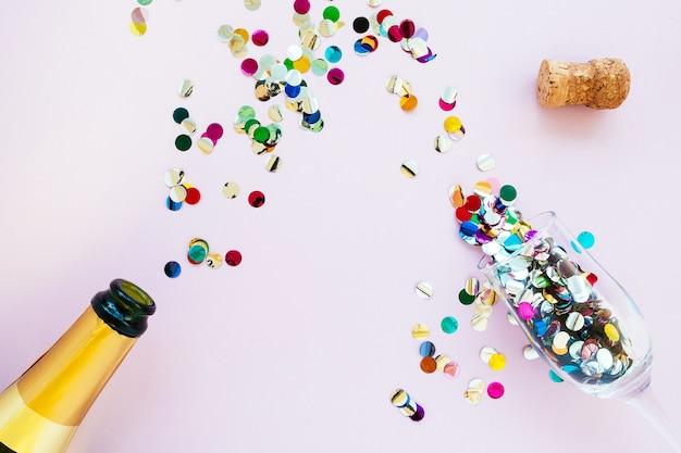 Золотая бутылка шампанского и бокалы с конфетти на розовом фоне