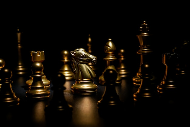 Gold chess on black background , focus on knight
