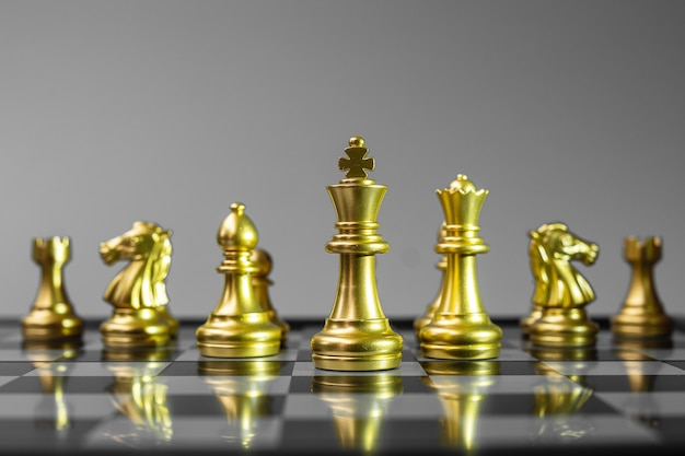 Gold chess figure team on chessboard.