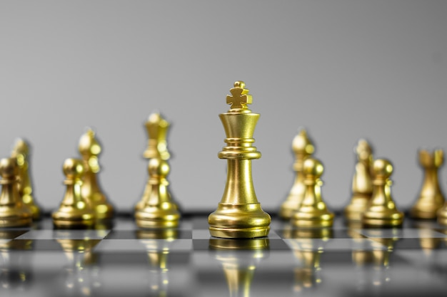 Gold chess figure team (king, queen, bishop, knight, rook and pawn) on chessboard against opponent during battle.