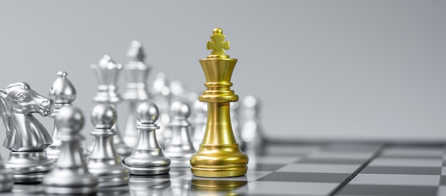 Gold chess king figure on chessboard against opponent or enemy.