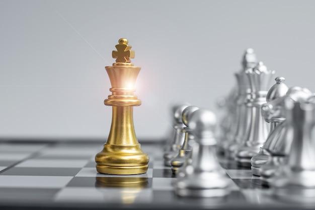 Золотая фигура шахматного короля на шахматной доске