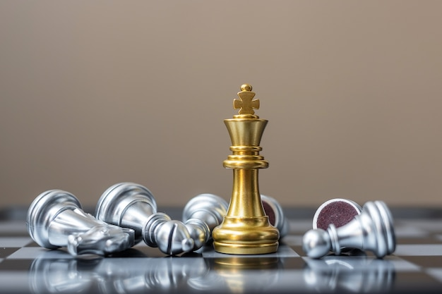 Gold chess king figure stand out from crowd of enemy during chessboard competition.