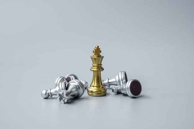 Gold chess king figure stand out from crowd of enemy or opponent during chessboard.
