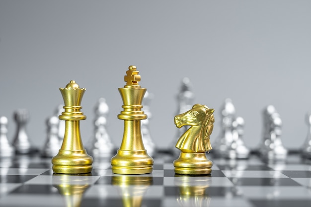 Gold chess king, queen and knight (horse) figure on chessboard against opponent or enemy.
