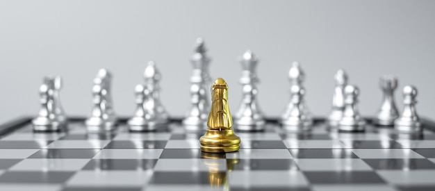 Золотой шахматный рыцарь фигура на шахматной доске против противника или врага.
