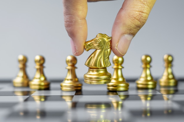 Gold chess knight figure stand out from the crowd on chessboard background.