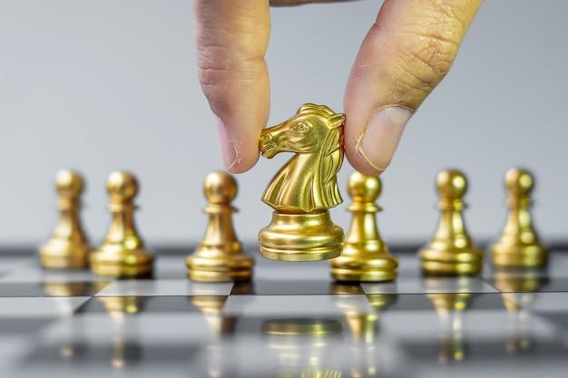 Фигурка золотого шахматного рыцаря выделитесь из толпы на фоне шахматной доски.