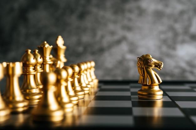 Золотые шахматы на шахматной настольной игре для концепции лидерства в метафоре бизнеса