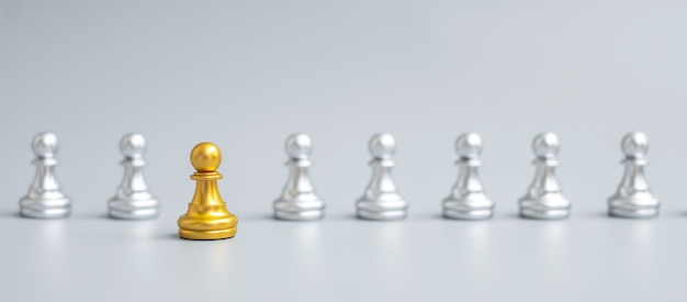 Золотая фигура шахматной пешки выделитесь из толпы на фоне шахматной доски. стратегия, лидерство, бизнес, командная работа, разные, уникальная концепция управления человеческими ресурсами