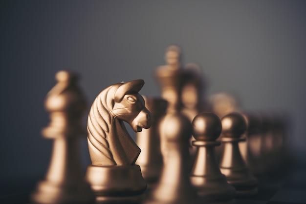 Золотые шахматные фигуры на шахматной доске.