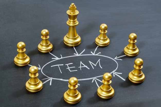 Gold chess team and the word team on chalkboard