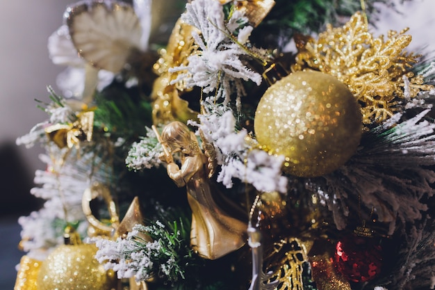 Gold christmas background of de-focused lights with decorated tree.