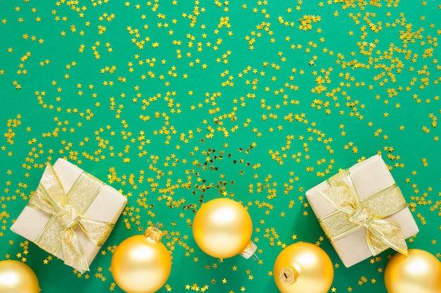 緑の表面に金色のクリスマス ボールとギフト ボックス、金色の星がきらめき、平置き、平面図