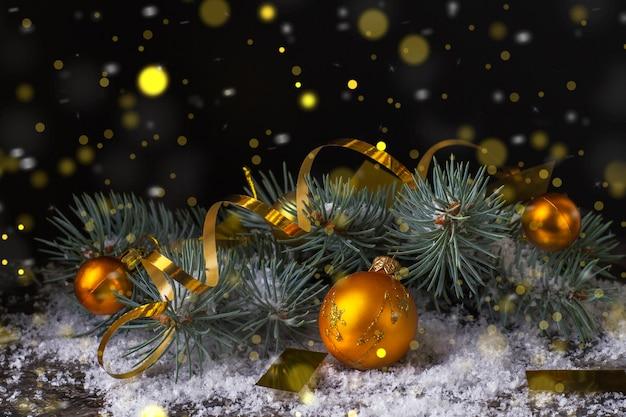 金のボケライトと黒の背景に金のクリスマスボールと金の蛇紋石。