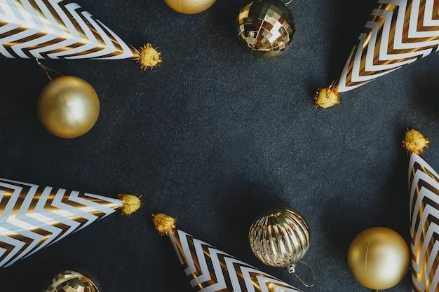 黒の背景にゴールドのクリスマスボールとパーティーキャップ。