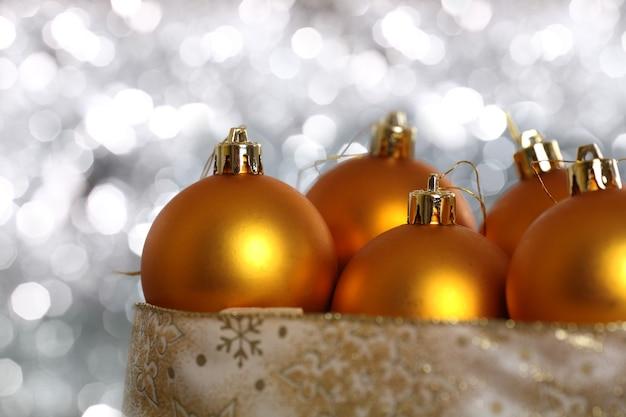 ぼやけた背景のボックスにゴールドのクリスマスボール