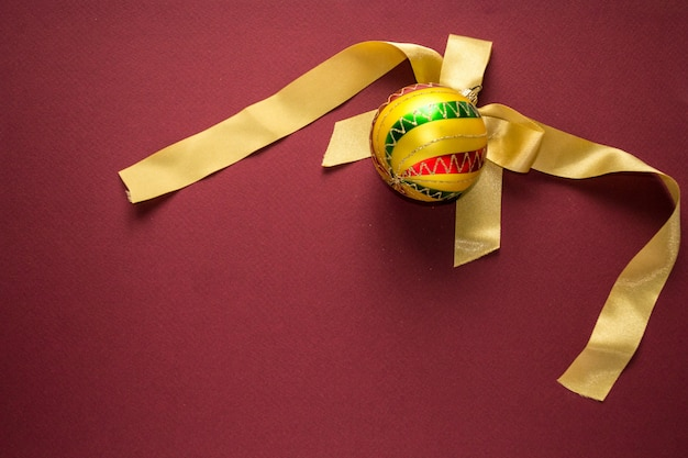 Gold christmas new year ball decoration with colorful stripes with from tree on bordo back
