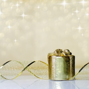 Gold christmas ribbon ornament on background of defocused golden lights. shallow dof.