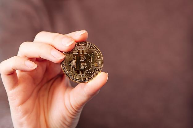 ゴールドコインビットコイン暗号通貨。暗号通貨のシンボルを手に持っています。