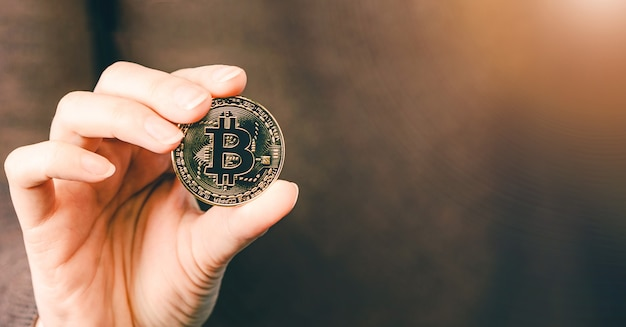 Золотая монета биткойн криптовалюта в руке. символ криптовалюты - электронные виртуальные деньги. платежи,