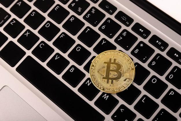 금화 bitcoin, 노트북, 키보드에 놓여 있습니다.