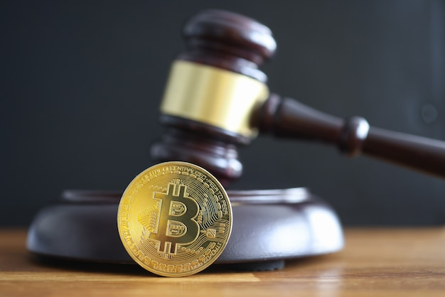 Gold coin bitcoin lying next to judge hammer closeup