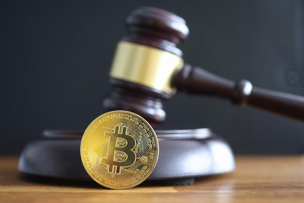 金貨のビットコインがハンマーのクローズアップを判断する隣に横たわっている