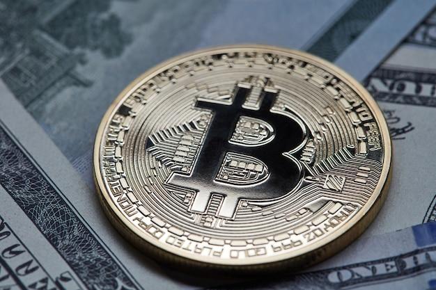 Золотая монета биткойн на многих банкнотах доллара сша