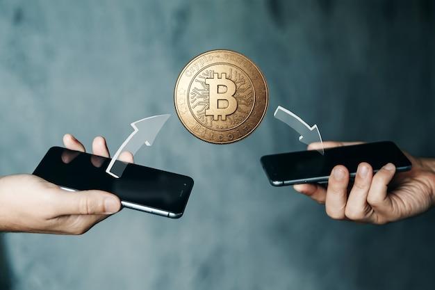 電話から電話、手、テレビのクローズアップへのゴールドコインビットコイン支払い。