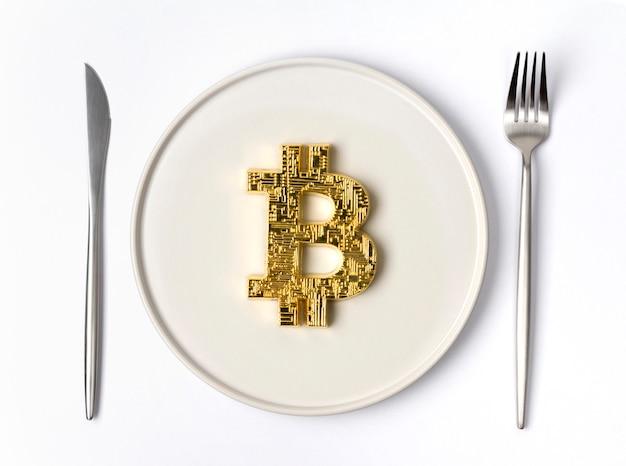 Золотая монета биткойн подается на белой пустой тарелке