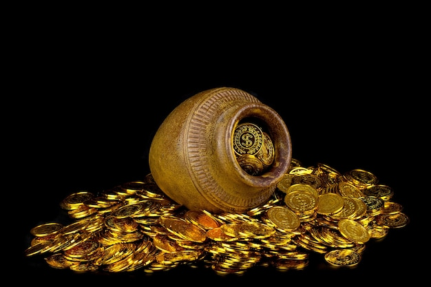 黒の背景に宝の古い鍋の金貨