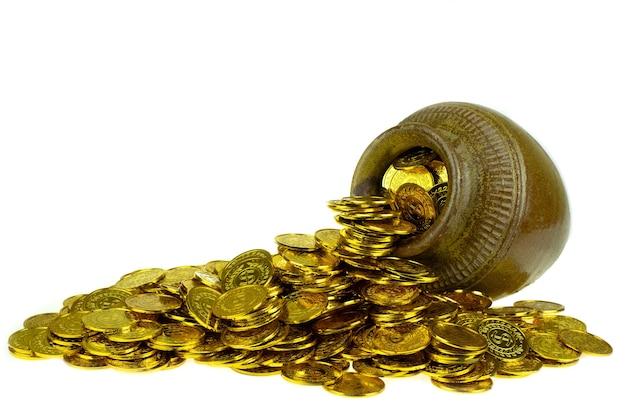 白い背景の上の宝の古い鍋の金貨