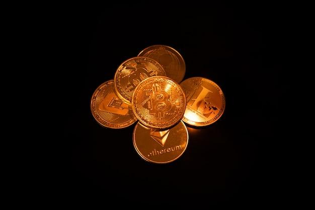 Золотые монеты различных криптовалют на черном фоне крупным планом, бизнес-концепция, виртуальные деньги, добыча.