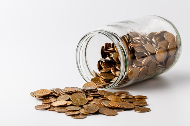 Gold coins spilling out of a jar on white background