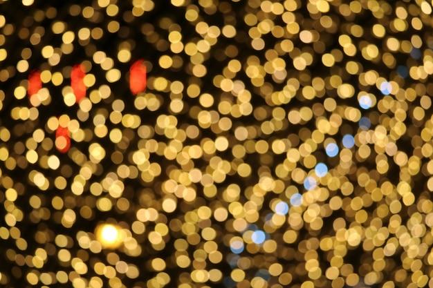 ゴールドカラーの抽象的なぼかしとボケ味のカラフルな光と夜の庭