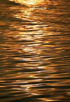 Поверхность морской воды золотого цвета с нежными волнами, блестящими от утреннего солнечного света