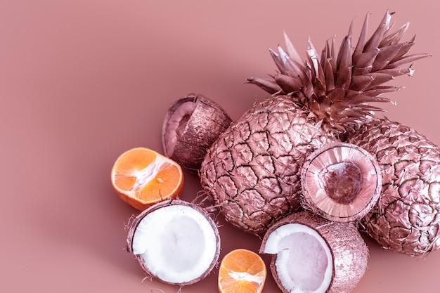 色付きの背景に金色の果物。トロピカルフラットレイ。食品のコンセプト。