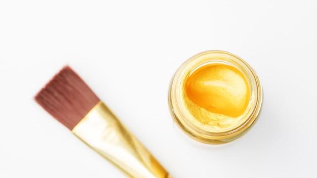 金色のポスター水彩ボトルと白い背景の上の絵筆。