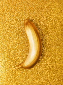 Gold colour food, golden banana on bright glitter or shimmer background