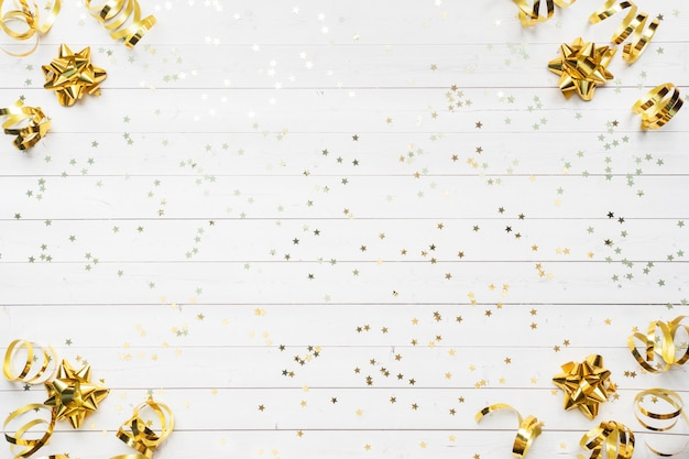 Gold confetti stars and ribbons on a white background.