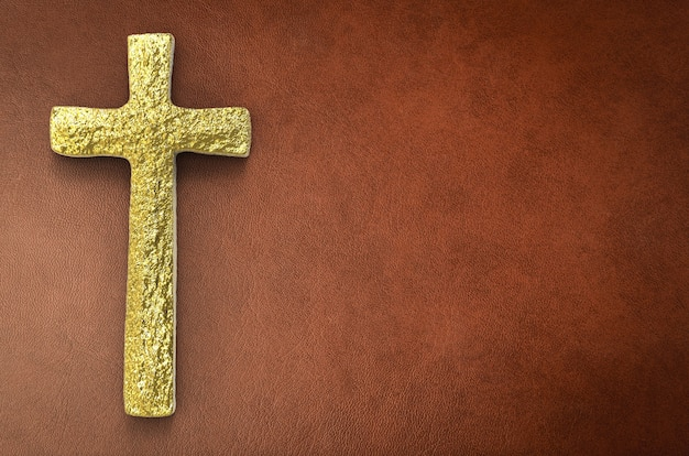 Gold cross with blank space on brown leather background