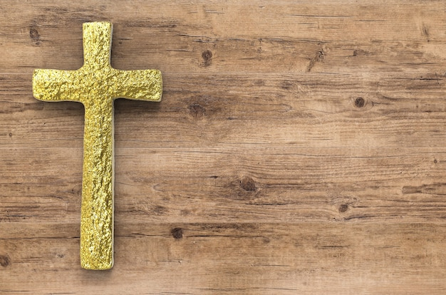 Gold cross with blank space on wooden background