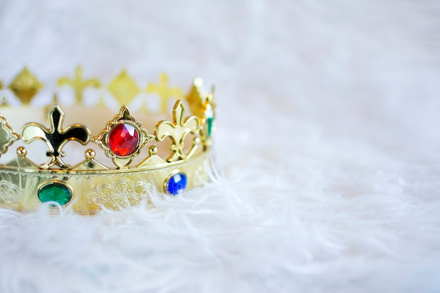Gold crown with colored gems. copyspace.